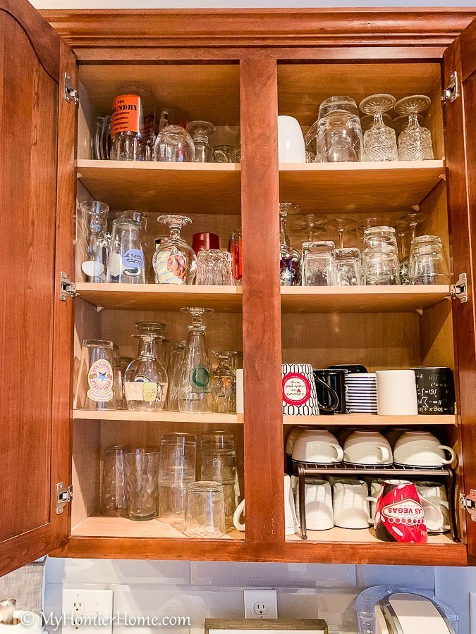 How to organize your kitchen cabinets using clear and simple strategies to tackle kitchen cabinet dysfunction without losing your mind. This is the before photo of the massive amount of cups we had in one cabinet.