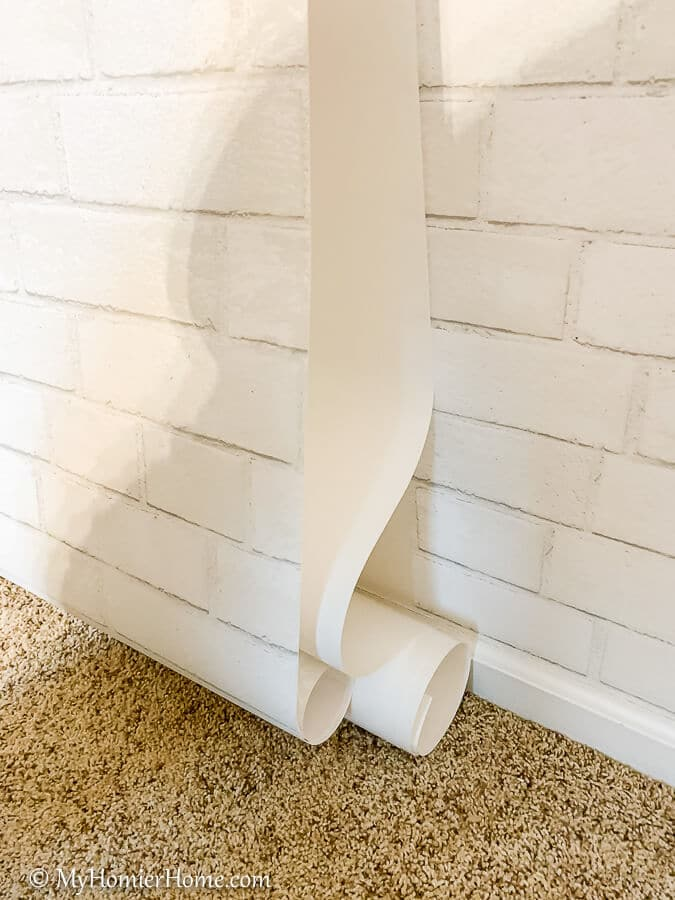 Continue the process of adhering the peel and stick wallpaper to the wall until you reach the bottom.