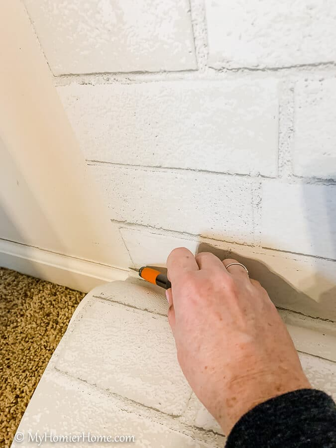 Use your X-acto knife to make a perfect cut following the baseboard.