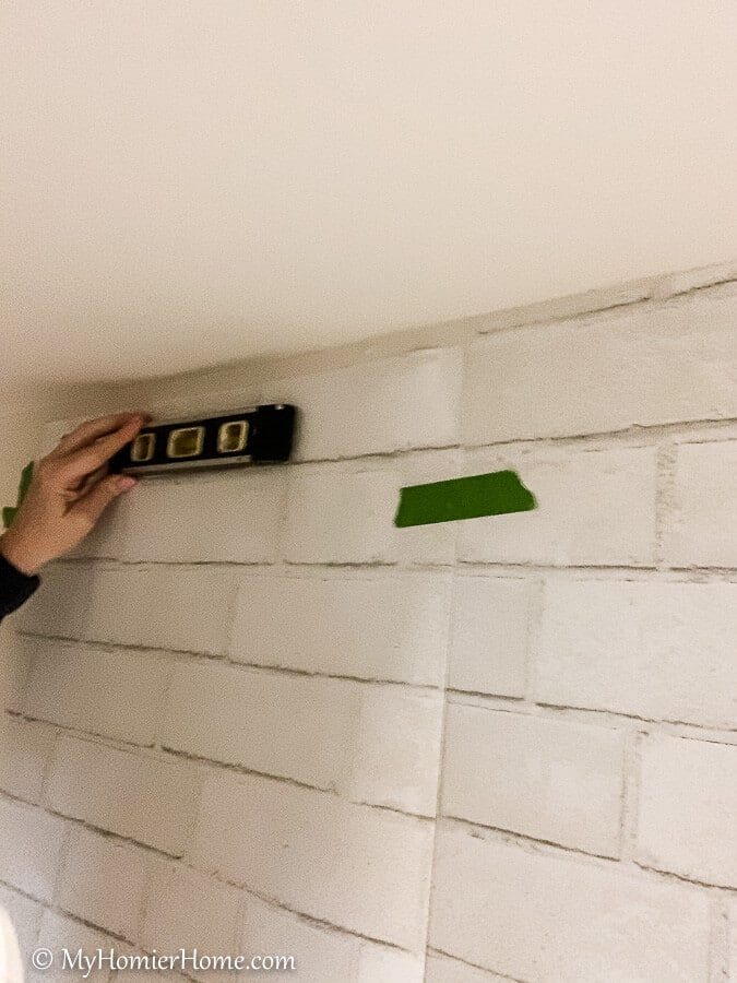 Adjust the peel and stick wallpaper using a level to make sure the design is straight.