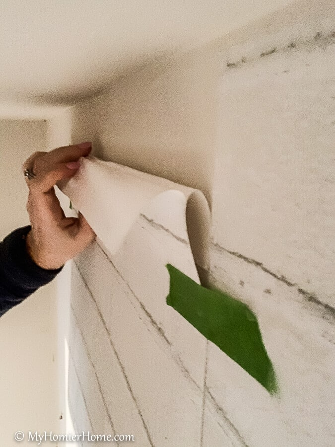 Fold the backing under to attach the peel and stick wallpaper to the wall.