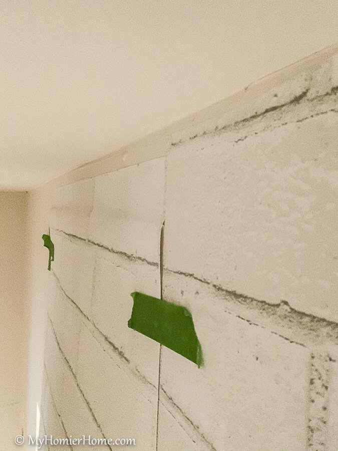 Stick the peel and stick wallpaper to the wall at the top.